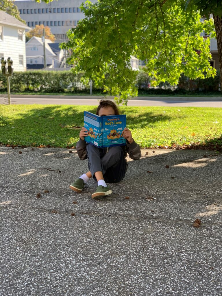 Child sitting out in the Towson Presbyterian Church parking lot wearing a mask and reading a Christian book for Church School