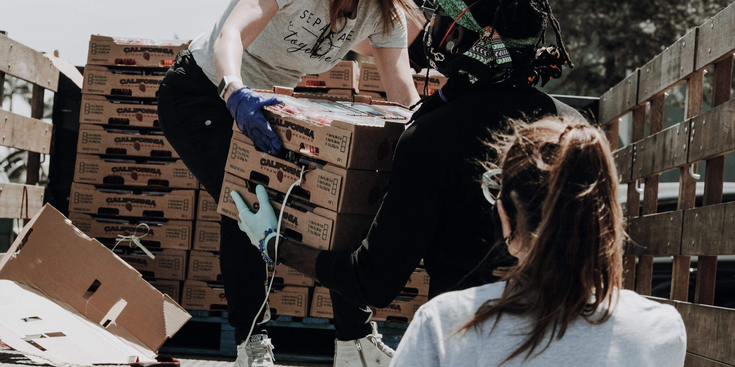 Three people in masks loading boxes off of a truck during a volunteer effort.